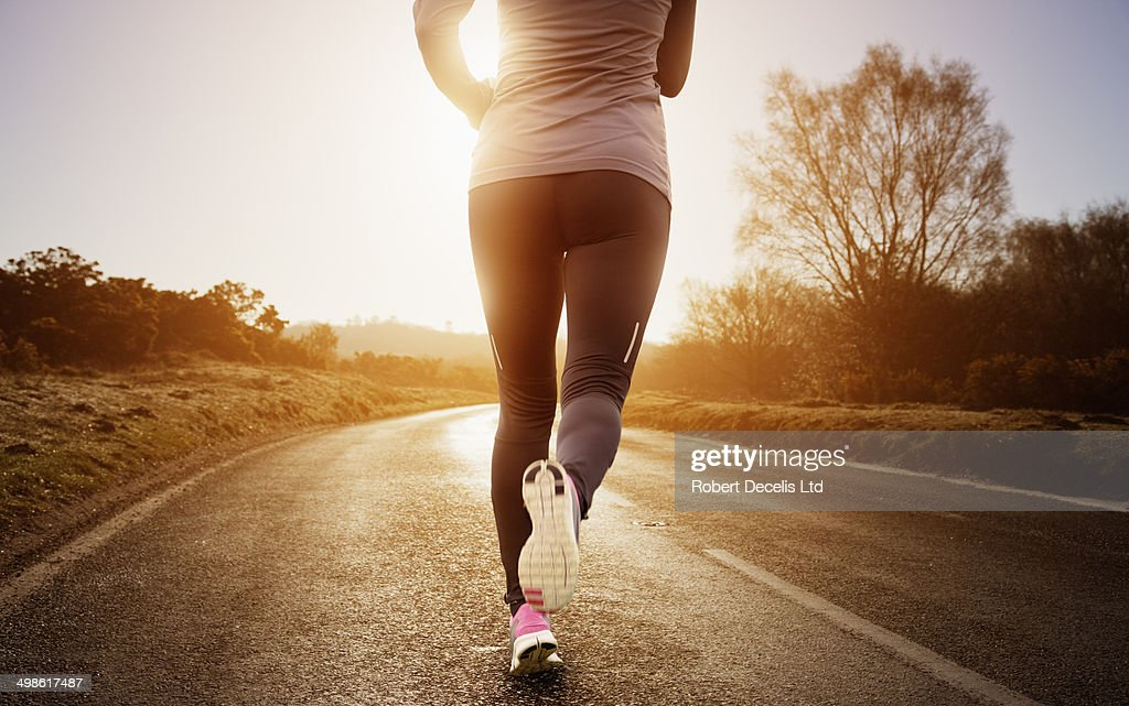 Female runner running along road : Stock Photo