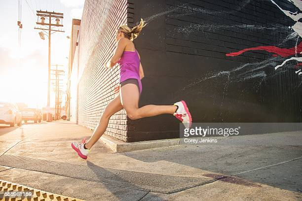 Female runner running along sidewalk