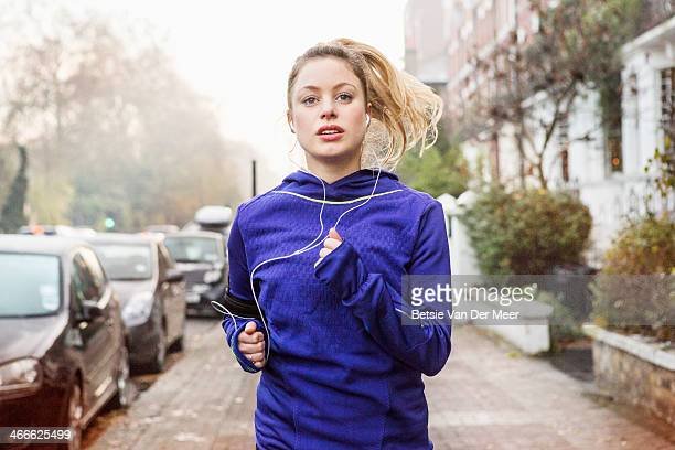 female runner running down urban street. - jogging stock pictures, royalty-free photos & images