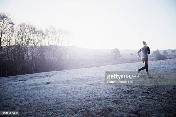 Female runner running through frosty, misty field