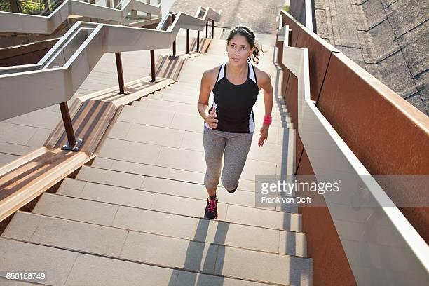 Female runner running up urban stairway