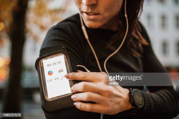 female runner setting up her mobile phone app before training - arm band stock pictures, royalty-free photos & images