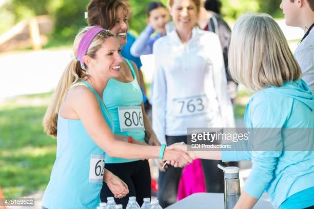 Female runner shaking hands while registering for marathon or 5k