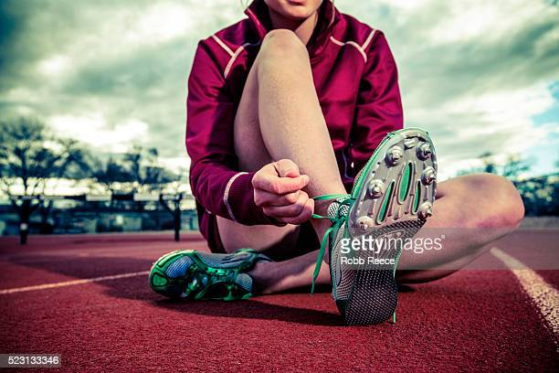 female runner sitting and tying track shoes - robb reece 個照片及圖片檔