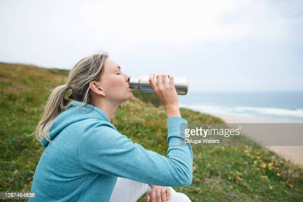 female runner sitting on coastline drinking from water bottle. - dougal waters stock pictures, royalty-free photos & images