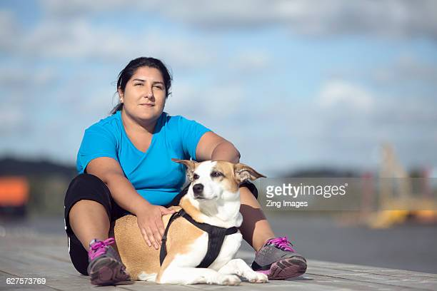 Female runner sitting with dog