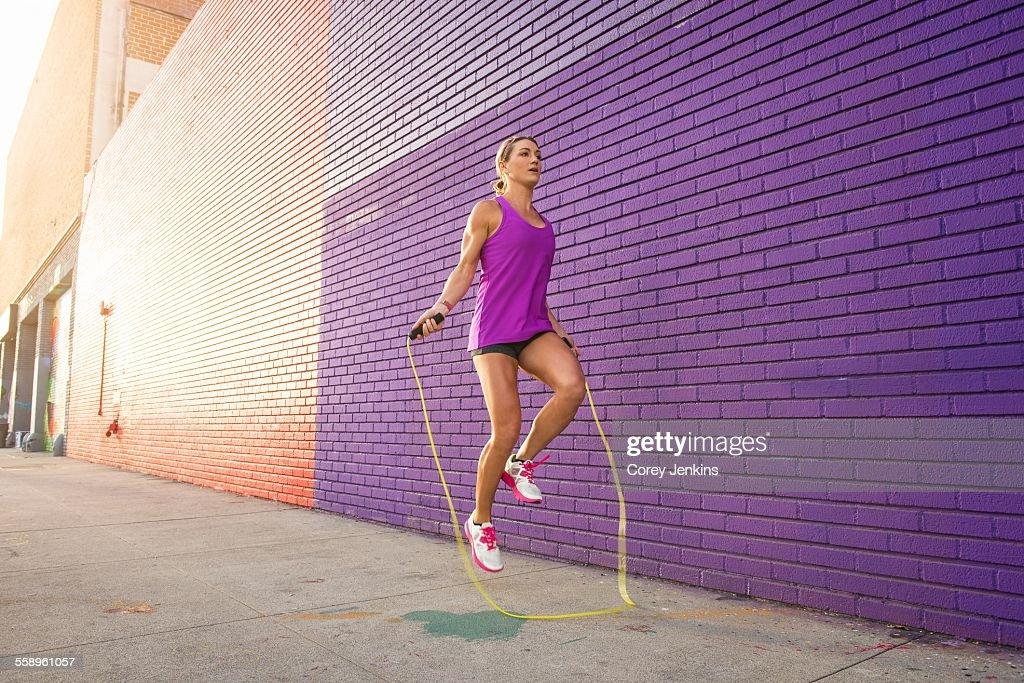 Female runner skipping on sidewalk : Stock Photo