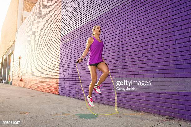 Female runner skipping on sidewalk