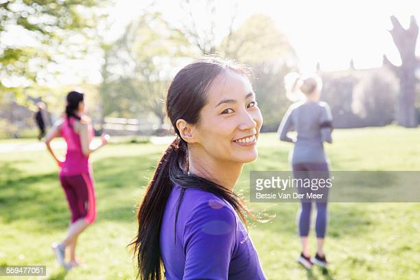 Female runner smiles to camera, following runners