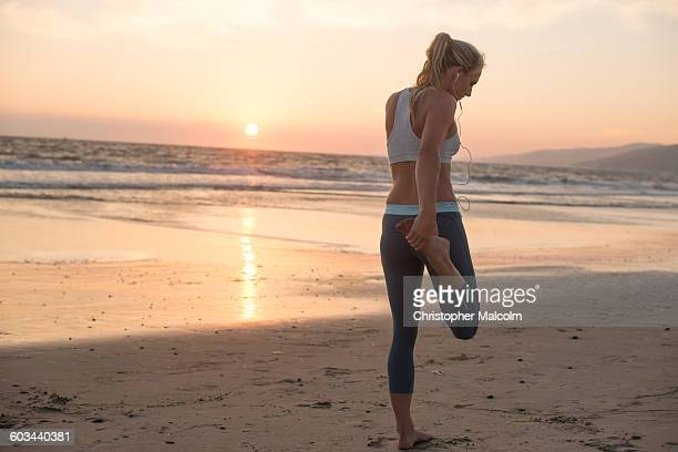 Female runner stretches at sunset