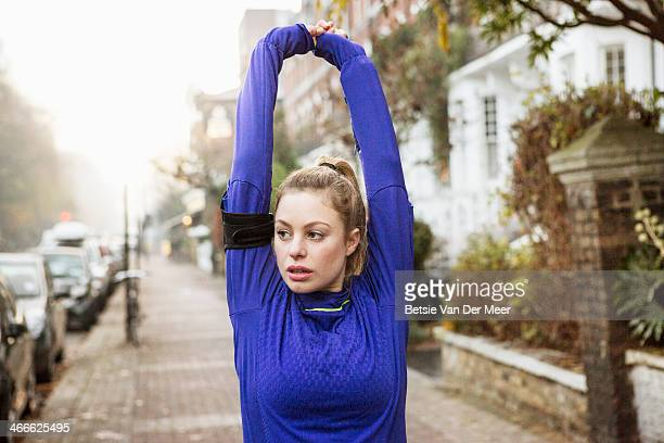 female runner stretching arms and back in street. - jogging stock pictures, royalty-free photos & images
