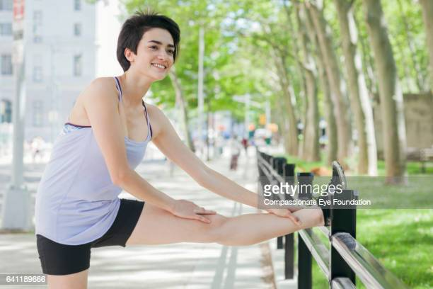 female runner stretching in park - running shorts stock pictures, royalty-free photos & images