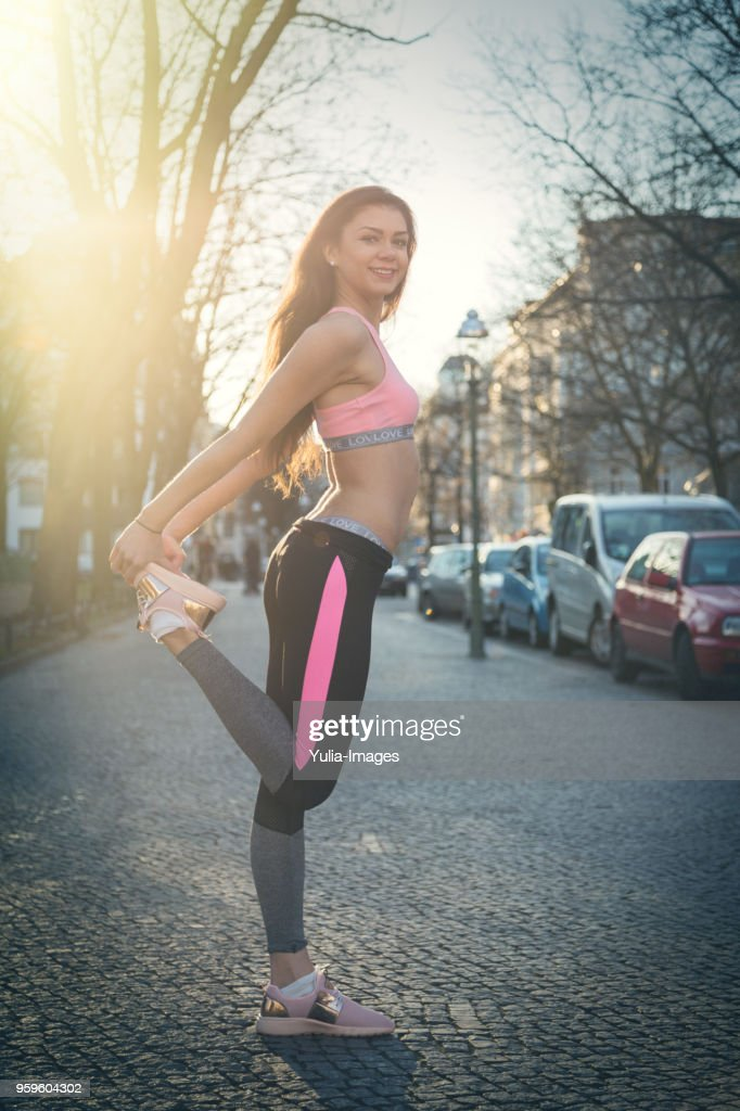 Female runner stretching in street : Stock-Foto
