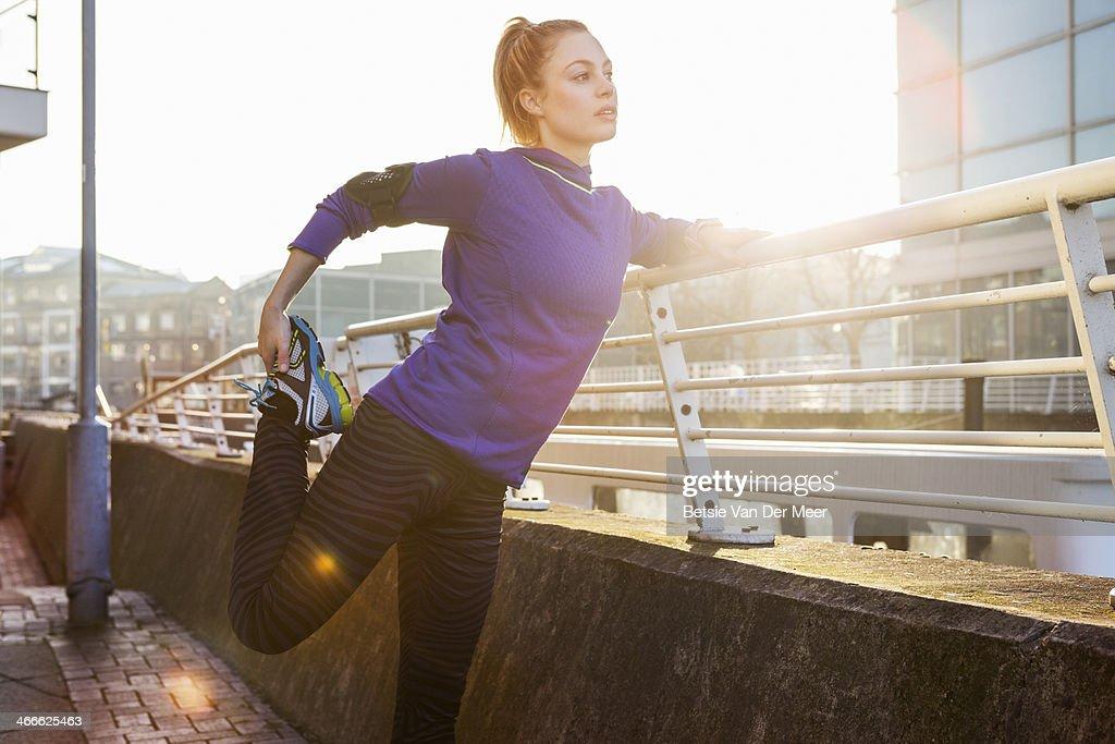 female runner stretching leg in urban space. : Stock Photo