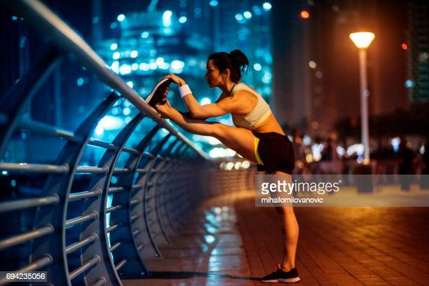 Female runner stretching legs