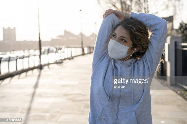 female runner stretching outdoors before her workout and wearing a facemask - state of emergency stock pictures, royalty-free photos & images