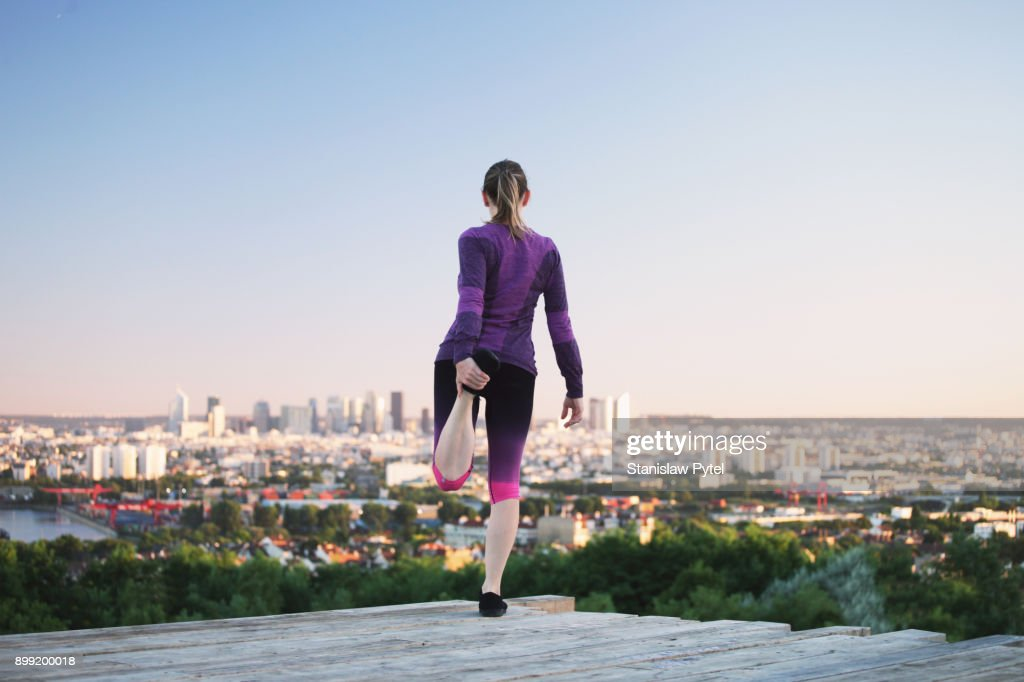Female runner stretching, Paris in background