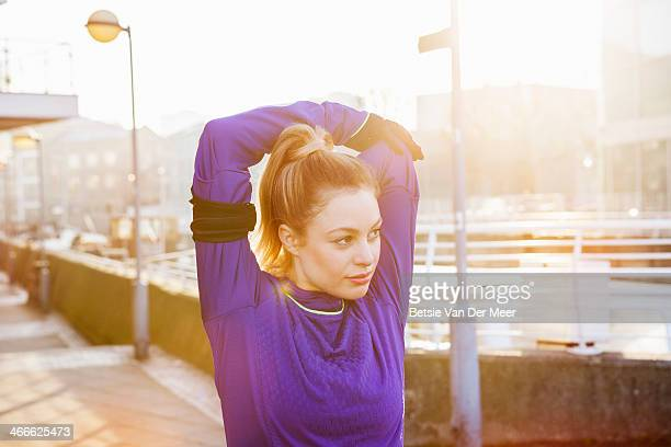 female runner stretching shoulders on street. - jogging stock pictures, royalty-free photos & images