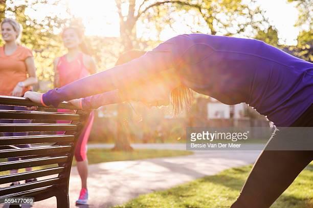 Female runner  stretching using parkbench