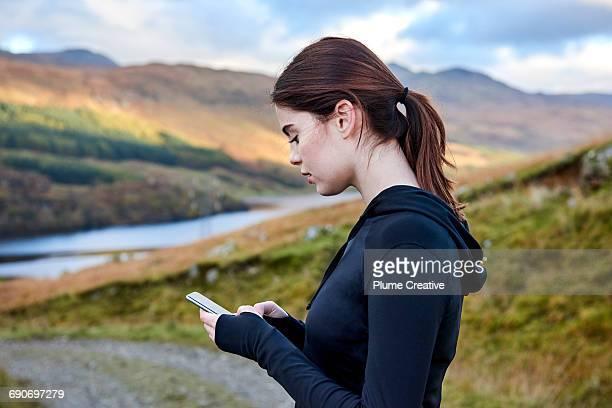 Female runner taking a break - checking her phone