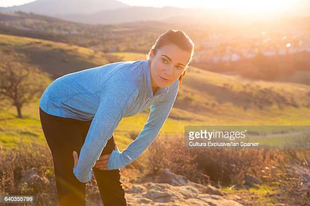 Female runner taking a break on mountain trail at sunset