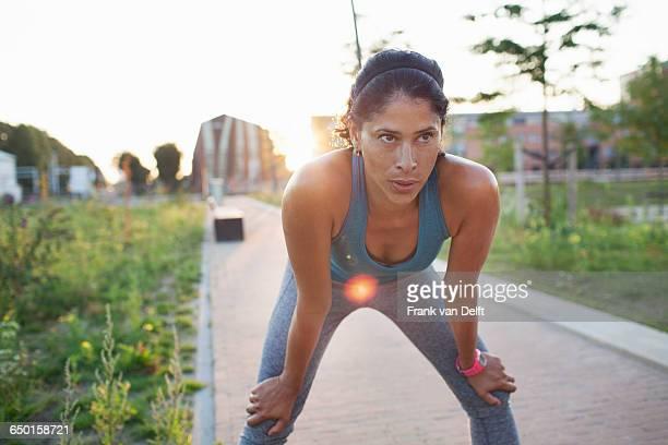 Female runner taking a break on sidewalk