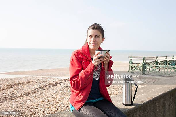 female runner taking a coffee break on wall at brighton beach - brighton beach england stock pictures, royalty-free photos & images