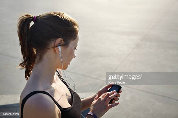 Female runner tjecking results on her smartphone