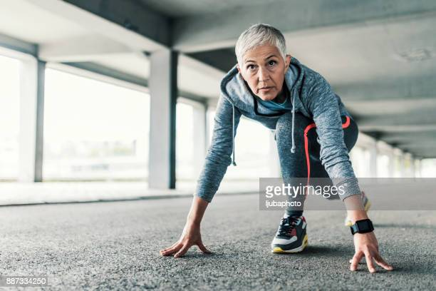 female runner training in starting position - women's track stock photos and pictures