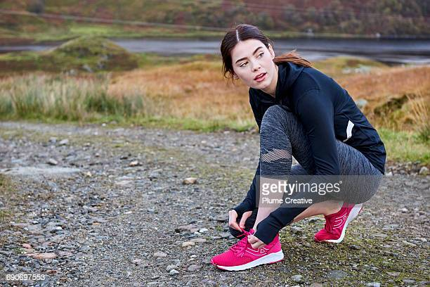 Female runner tying her shoe laces