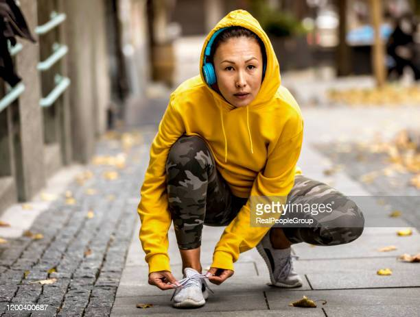 female runner tying her shoes and preparing for a jogging - yellow shoe stock pictures, royalty-free photos & images
