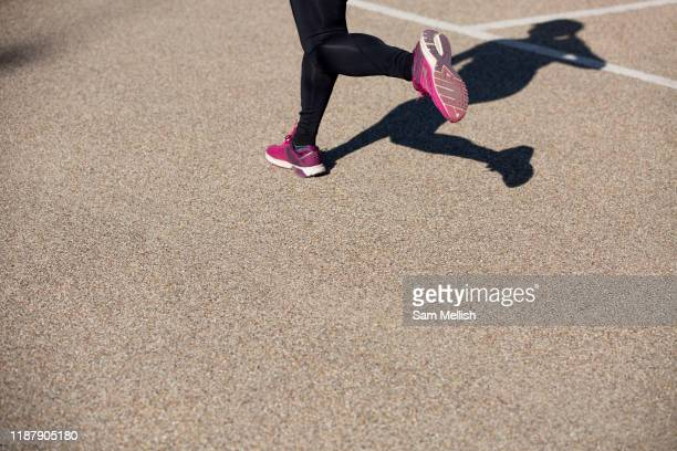 Female runner wearing black leggings and pink running trainers taking part in a 10 kilometre running event at the Queen Elizabeth Olympic Park on the...