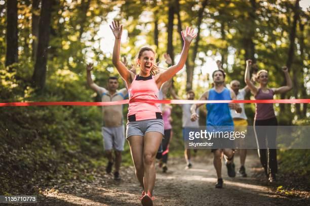 女性ランナーワインマラソンレースと腕を上げた交差フィニッシュライン. - ハーフマラソン ストックフォトと画像