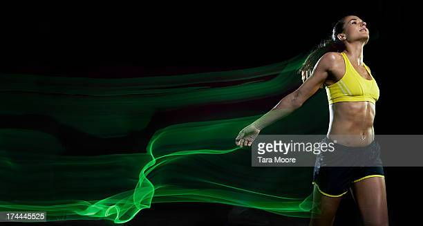 female runner winning race with light trails