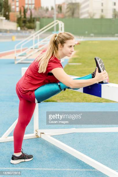 female runner with prosthesis stretching legs at stadium - leaning disability stock pictures, royalty-free photos & images