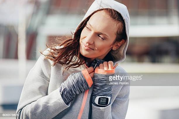 Female runner zipping up hoody in city