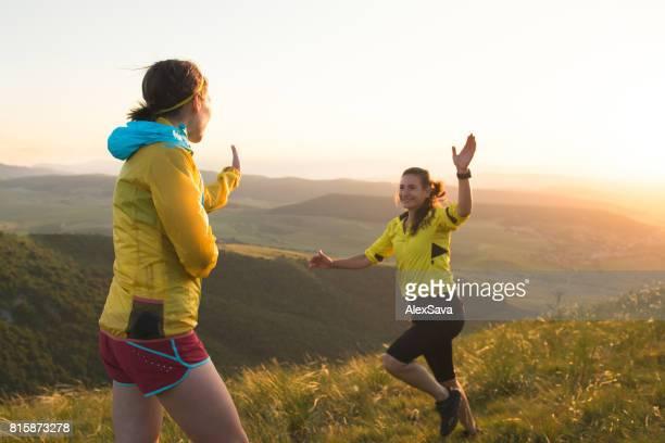 vrouwelijke lopers vieren hun acomplishment met een hoge vijf - pets stockfoto's en -beelden