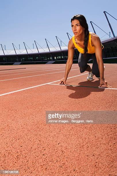 Female runners on starting block at stadium