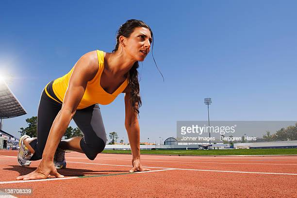female runners on starting block at stadium - center athlete stock pictures, royalty-free photos & images