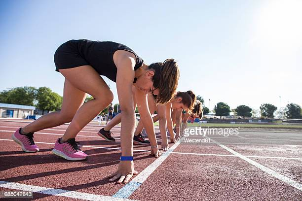 Female runners on tartan track in starting position