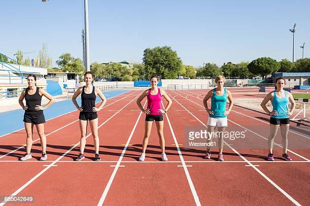 Female runners standing on tartan track at starting line
