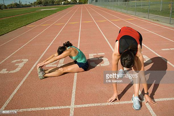 Female runners stretching on track, Utah, United States