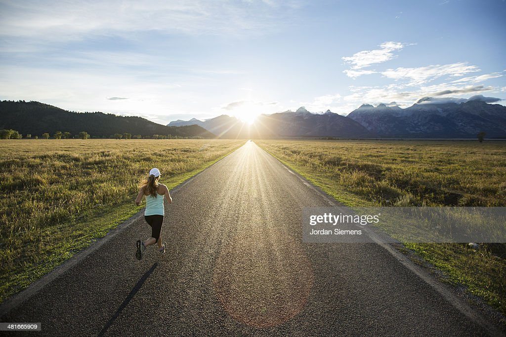 A female running at sunset. : Stockfoto