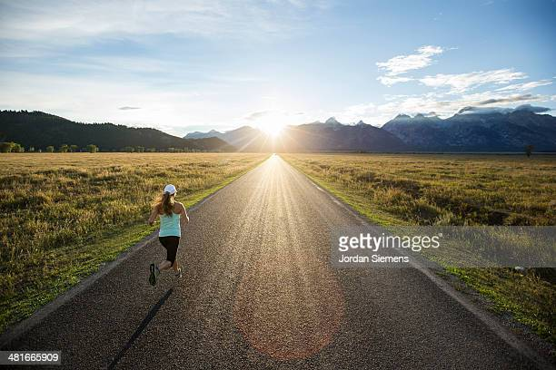 a female running at sunset. - long hair stock pictures, royalty-free photos & images