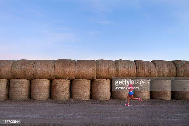 A female running in front of hay bails.