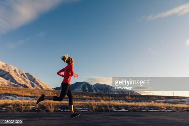 冬の終わりに実行する女性 - ハーフマラソン ストックフォトと画像