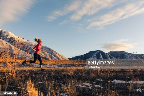 female running in late winter - half_marathon stock pictures, royalty-free photos & images