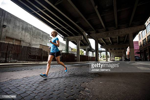 a female running in the city. - joggeuse photos et images de collection