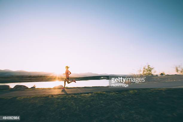 female running on path during sunset in utah - sunset lake stock photos and pictures