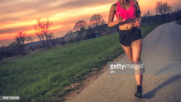 Female running on the road in dusk
